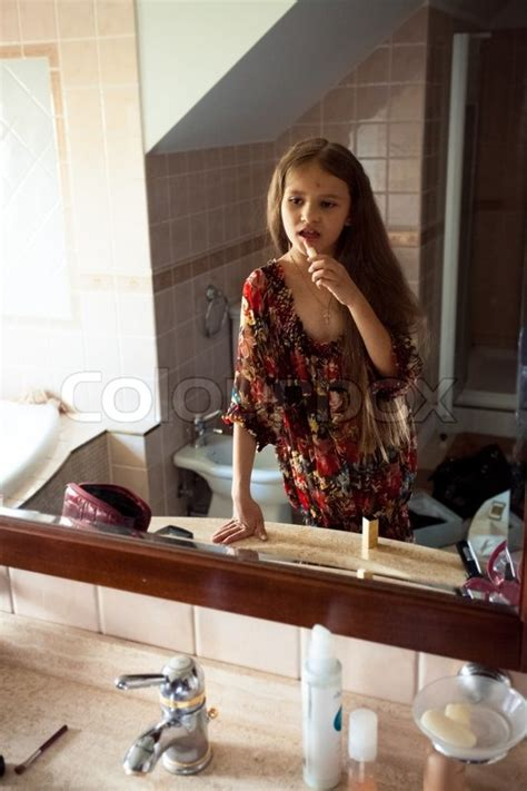 Little cute girl looking at mirror and